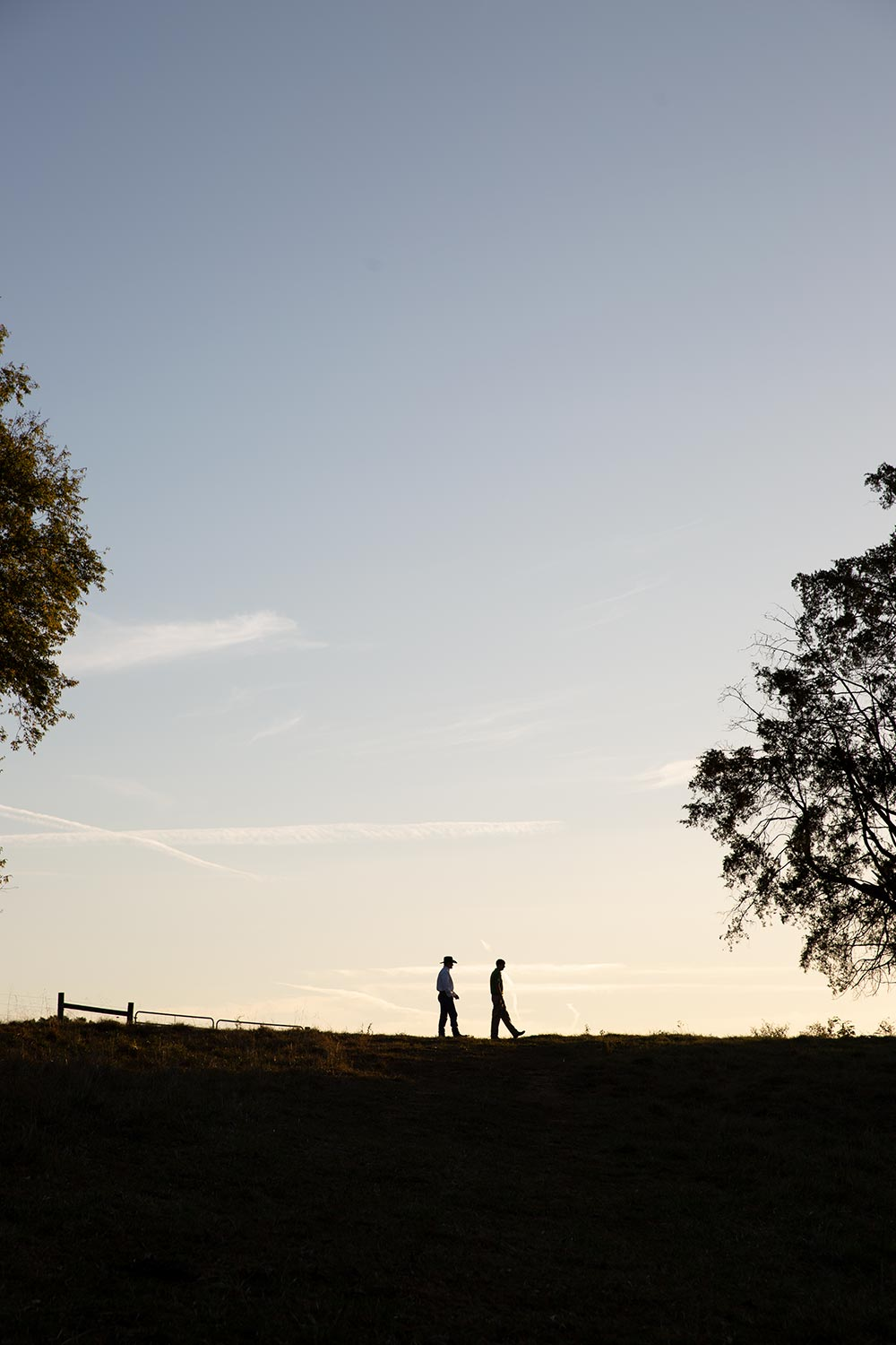 Silhouette of two people walking in the distance at sunset